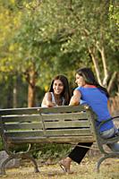 Two teen girls sitting on park bench - Alex Mares-Manton