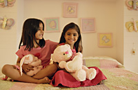 little girls with stuff bears on bed - Alex Mares-Manton