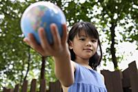 Girl holding out globe - Yukmin