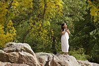 girl in white sari, standing in yoga pose on rock - Alex Mares-Manton