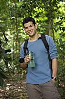 Man wearing a backpack, holding water bottle - Yukmin