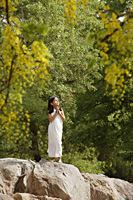 girl in white sari, standing in yoga pose on rock - Alex Mares-Manton