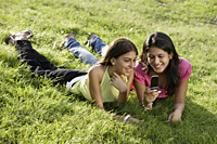 two teen girls in park, looking at text messages - Alex Mares-Manton