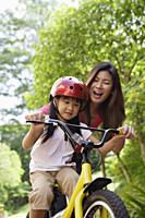 Mother teaching daughter to ride bicycle - Yukmin