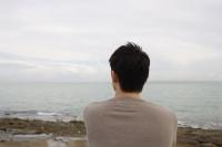 Man sitting seaside looking out to ocean - Yukmin