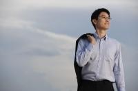 Businessman standing with jacket over shoulder - Yukmin