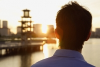 Young man looking into city skyline - Yukmin