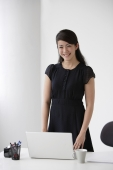 Young woman standing at desk - Yukmin