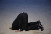Businessman with head buried in sand - Yukmin