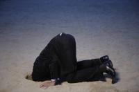 Businessman with head buried in sand - Yukmin