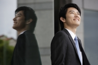 Profile and reflection of businessman smiling - Yukmin