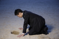 Businessman looking into hole in sand - Yukmin