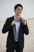 Businessman on beach, removing tie - Yukmin