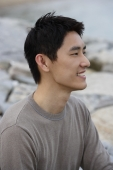 Profile of man sitting on seashore - Yukmin