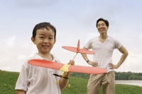 Father watching son holding toy airplane - Yukmin