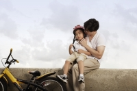 Father hugging son after bike ride - Yukmin