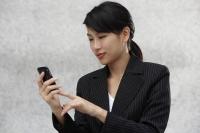 Businesswoman using hand held device - Yukmin