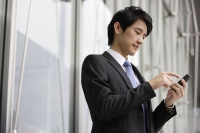 Businessman sending message on mobile device - Yukmin