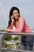 Young woman leaning over bridge on cell phone - Yukmin