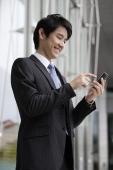 Businessman sending message on mobile device - Yukmin