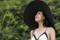 Young woman wearing big black hat - Yukmin