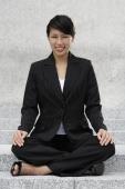 Businesswoman sitting crossed-legged outside - Yukmin