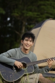 Young man playing guitar in front of tent - Yukmin