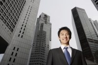 Portrait of businessman among buildings - Yukmin