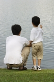 Father and son looking at lake - Yukmin