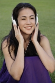 Portrait of young woman listening to music at park - Yukmin