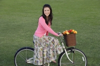 Young woman riding bike with basket full of flowers - Yukmin