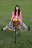 Young woman riding bike with legs kicked out - Yukmin