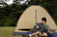 Young man playing guitar outside of tent - Yukmin