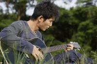 Young man playing guitar in grass - Yukmin