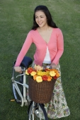 Young woman pushing bike with basket full of flowers - Yukmin