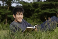 Young man reading in grass - Yukmin