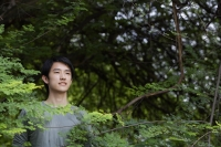 Young man standing in foliage - Yukmin