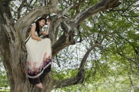 Young woman sitting in tree - Yukmin