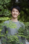Young man smiling behind foliage - Yukmin