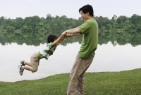 Father swinging son by arms - Yukmin