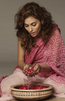 Woman in sari cupping rose petals and rose water - Vivek Sharma