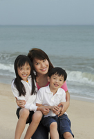 Young woman hugging boy and girl on beach - Yukmin