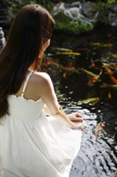Young woman in white dress sitting by pond - Nugene Chiang