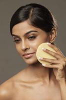 woman applying face powder - Vivek Sharma