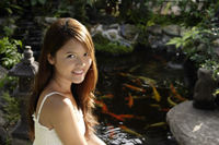 Young woman sitting by koi pond - Nugene Chiang