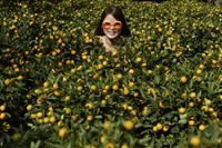 Young woman among orange plants - Nugene Chiang