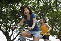 woman and young girl riding tandem bike - Yukmin