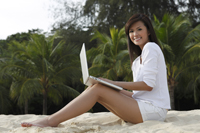 Young woman working on laptop on beach - Yukmin
