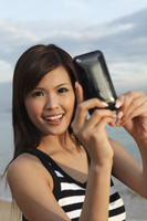 Young woman taking photo with camera phone - Yukmin