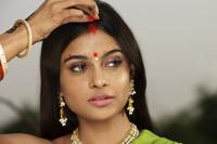 woman wearing sari, applying Sindoor powder down her hair part - Vivek Sharma